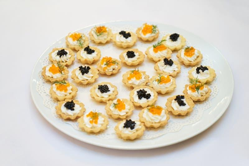 果子馅饼用在一块白色板材的黑和红色鱼子酱 免版税图库摄影