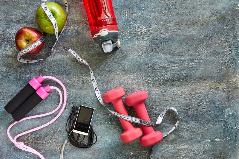 果子,哑铃,一个瓶水,绳索,米,蓝色背景的球员与污点 免版税图库摄影