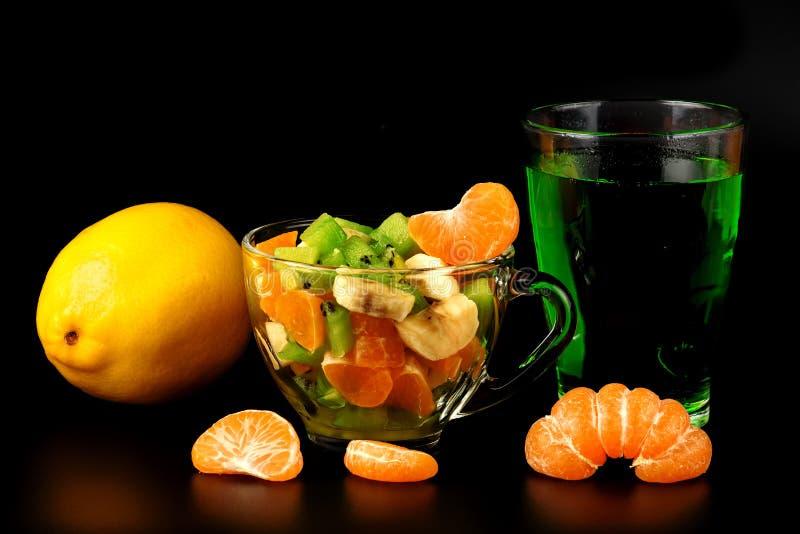 水果沙拉、蜜桔的柠檬、与饮料的段和玻璃 图库摄影