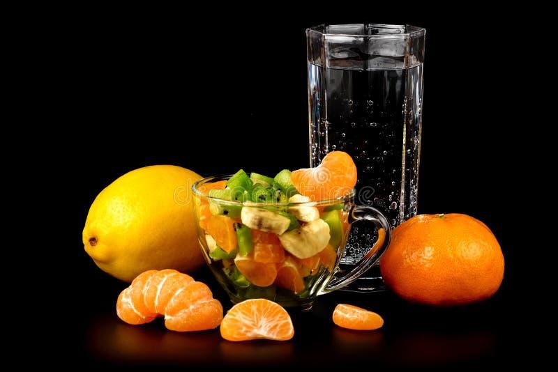 水果沙拉、蜜桔的柠檬、与饮料的段和玻璃 免版税库存图片