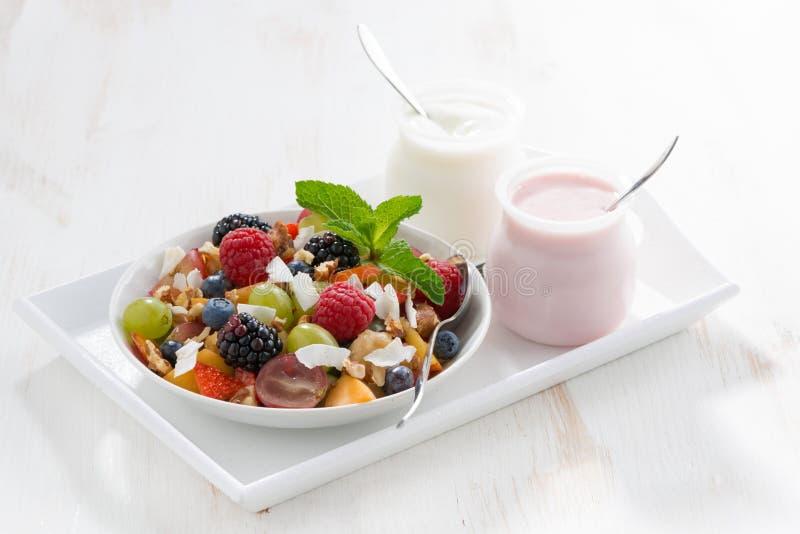 水果沙拉和各种各样的酸奶在一张白色木桌上 免版税库存照片