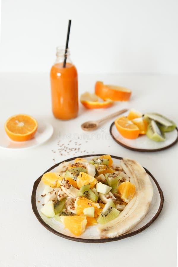水果沙拉用香蕉、桔子、猕猴桃和苹果在一块大板材 第二块板材切开用桔子和猕猴桃 免版税库存照片