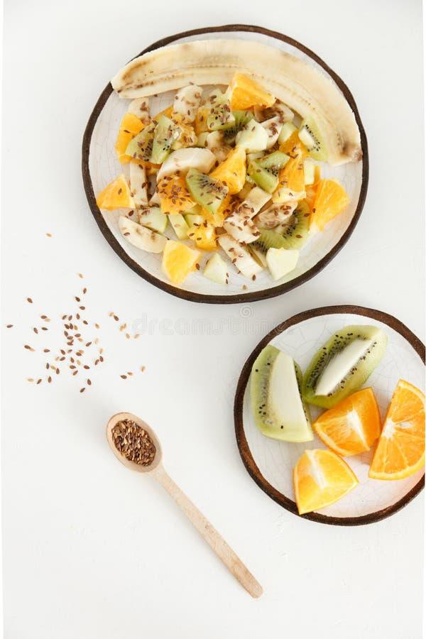 水果沙拉用香蕉、桔子、猕猴桃和苹果在一块大板材 第二块板材切开用桔子和猕猴桃 库存照片