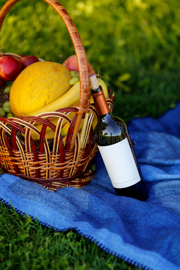 水果篮和瓶在自然的酒 库存照片