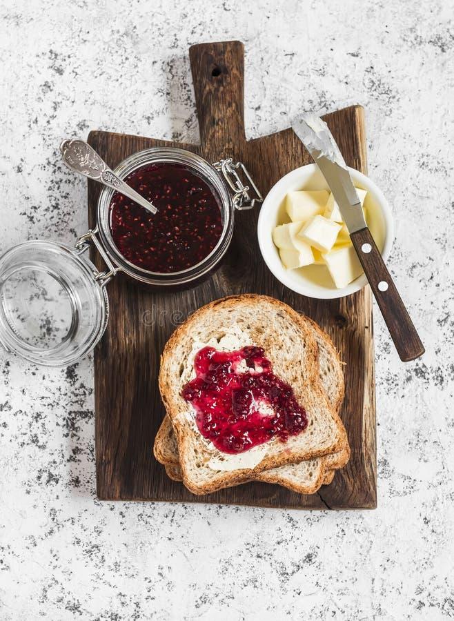 果酱,黄油,在木切板的多士面包在轻的背景 免版税库存图片