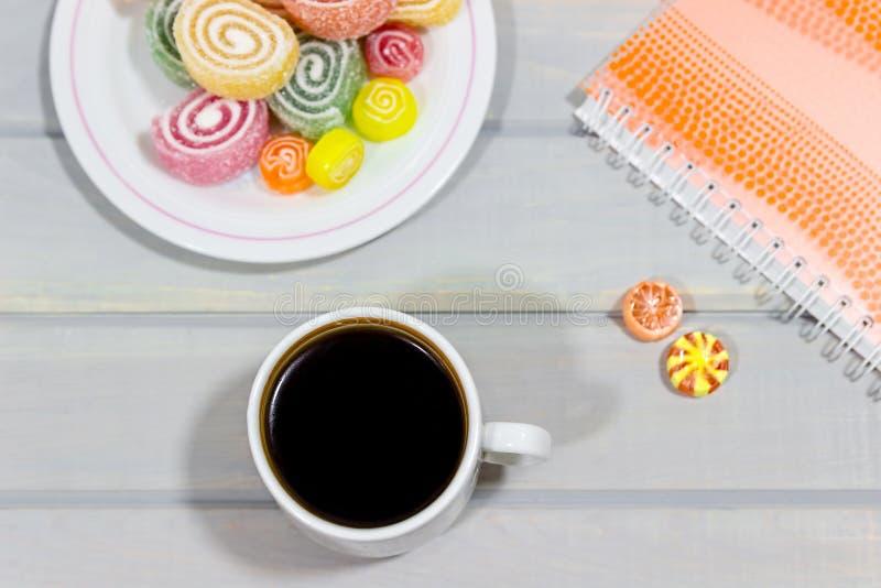果冻和一杯咖啡在一张灰色木桌上的 在背景的笔记本 n 免版税库存图片
