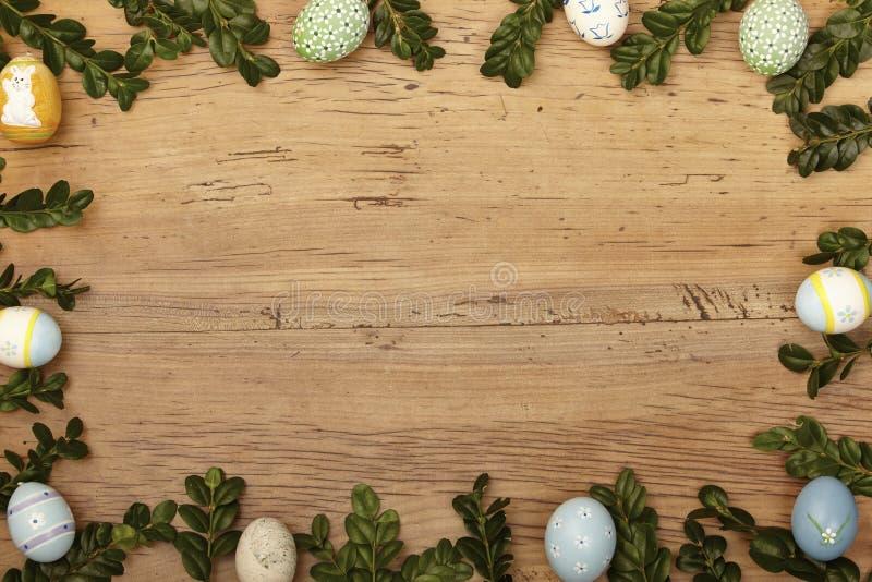 枝杈和复活节彩蛋作为框架在木头,拷贝空间 免版税库存图片