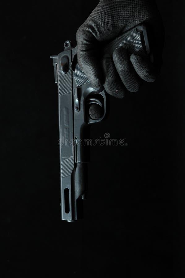 枪和一只手在黑色 图库摄影
