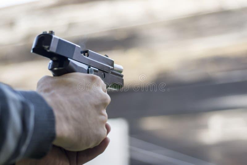 枪火街道攻击 射击从桶出来的手枪和烟 库存图片