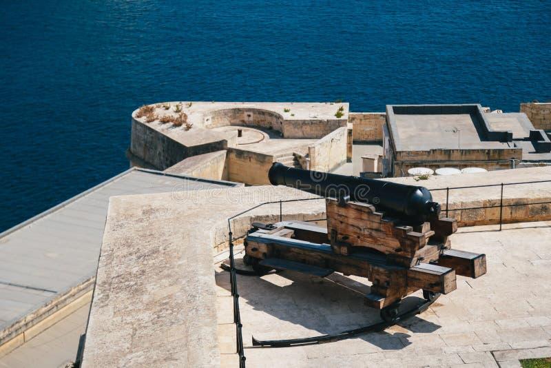 枪,从向致敬的电池的一门大炮在上部Barrakka庭院里在瓦莱塔,马耳他有盛大港口的一个权威的看法 库存图片
