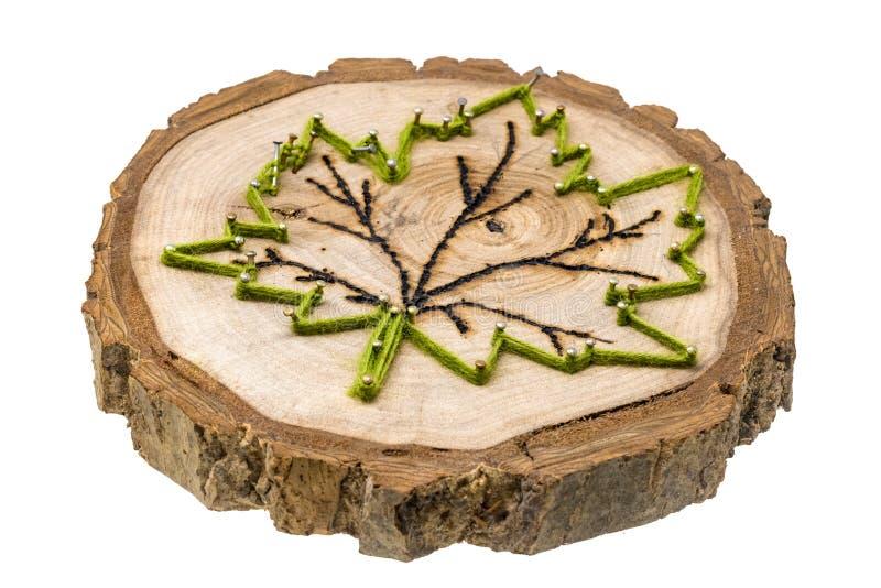 枫叶由羊毛和钉子做成在与手工制造的烙画的一个树切片 免版税库存图片