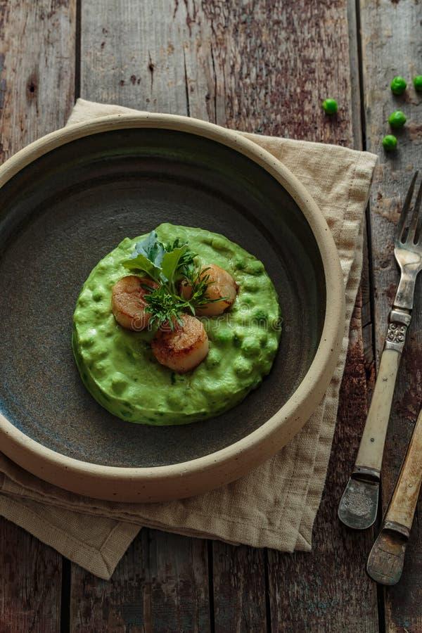枯萎的扇贝用在板材接近的视图的豌豆纯汁浓汤 免版税库存图片