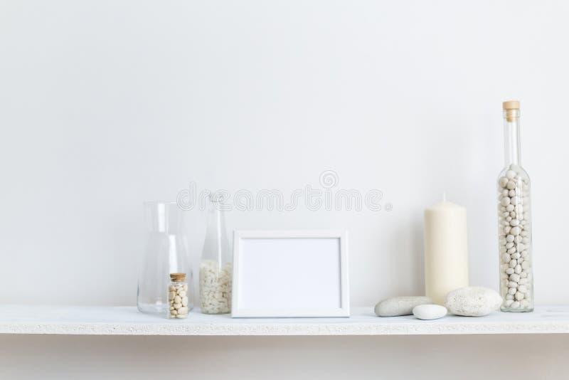 架子对有装饰蜡烛、玻璃和岩石的白色墙壁 库存图片