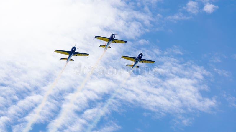 3架表现喷气机,一前一后飞行,在与白色云彩的一天空蔚蓝 免版税图库摄影