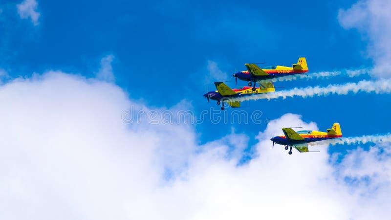 3架表现喷气机,一前一后飞行,在与白色云彩的一天空蔚蓝 库存图片