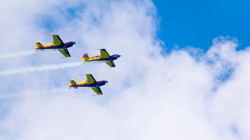 3架表现喷气机,一前一后飞行,在与白色云彩的一天空蔚蓝 免版税库存图片