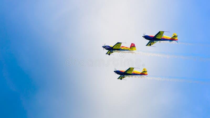 3架表现喷气机,一前一后飞行,在与白色云彩的一天空蔚蓝 免版税库存照片