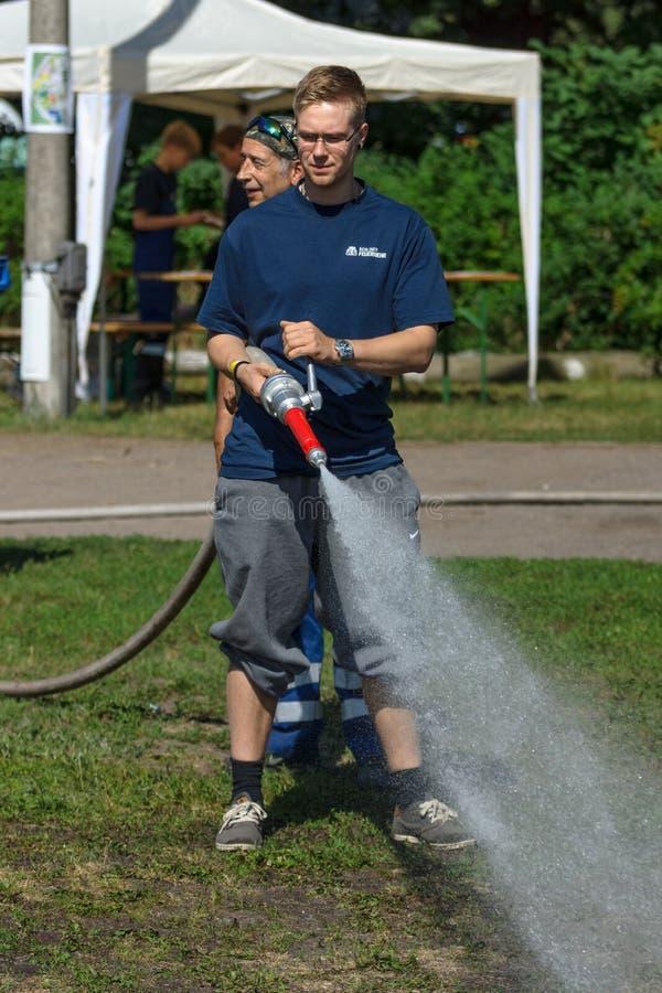 柏林消防队员显示技能与喷雾嘴一起使用 库存图片