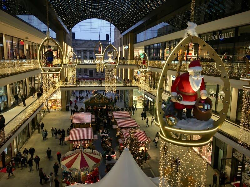 柏林购物中心为与的圣诞节装饰了大木圣诞老人项目,繁忙与许多顾客 免版税库存图片