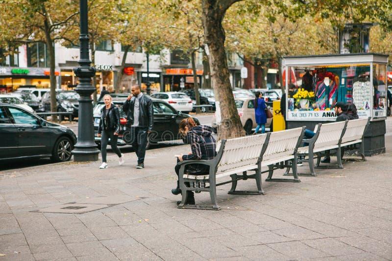 柏林, 2017年10月2日:漫步沿柏林街道的年轻不同种族的夫妇在人旁边坐长凳 免版税库存照片