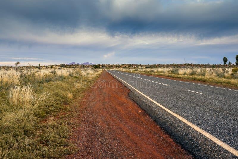 柏油碎石地面路导致无处在风雨如磐的云彩的澳大利亚沙漠 免版税图库摄影