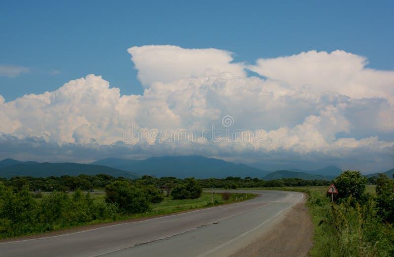 柏油碎石地面路舒展入距离 蓬松云彩和小山在背景 免版税库存照片