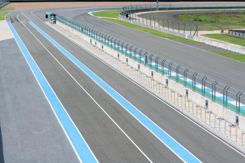柏油路与篱芭的车轨道在室外电路,与曲线路的赛马跑道赛车的 库存照片