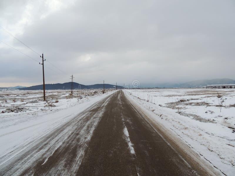 柏油路低谷多雪的领域 库存图片