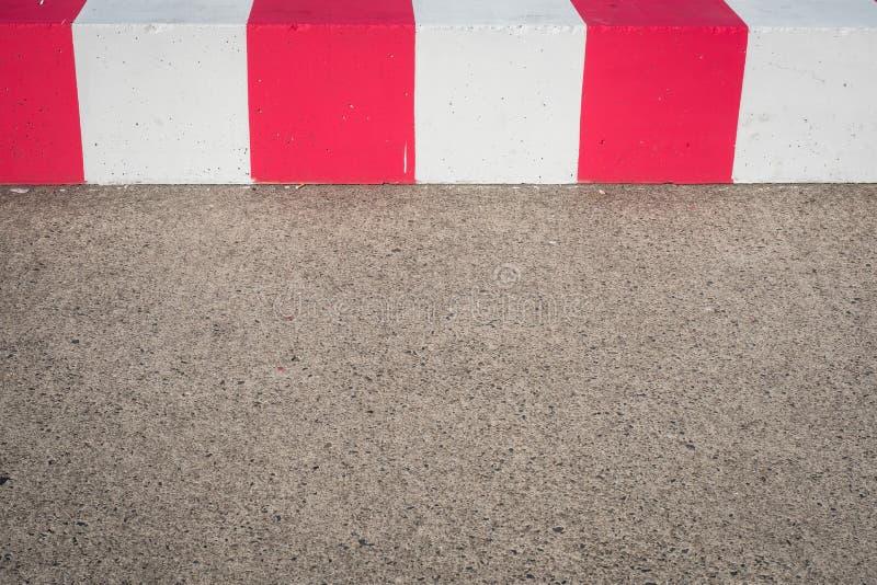 柏油路和红色,白色障碍/封锁在跑道前机场的- 库存照片