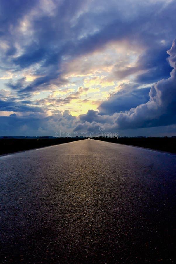 柏油路和黑暗的雷雨云在它 免版税库存图片