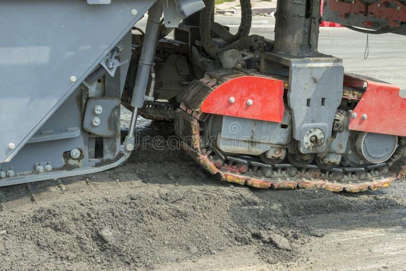 柏油路的机械 在工作者和涂柏油的机器的接近的看法 柏油路的机械 免版税图库摄影