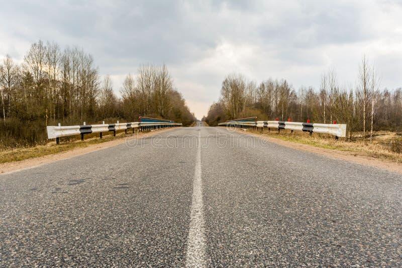 柏油路的看法横跨桥梁的有旁边修整器的,农村路通过森林 库存照片