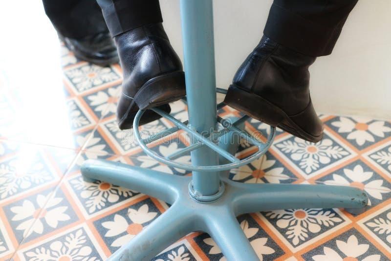 某些男性商人腿坐葡萄酒铁椅子 投入在黑鞋子 免版税库存图片