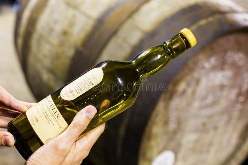 某人举行一个瓶16年年迈的Lagavulin唯一麦芽wh 免版税库存图片
