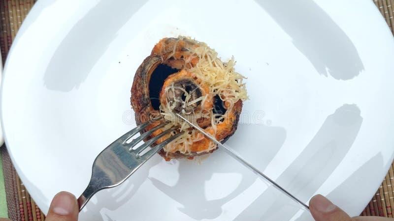 某人切除了被烘烤的蘑菇片断与叉子和刀子的 First-person?? 图库摄影