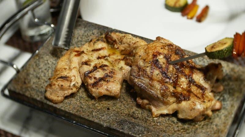 某人吃晚餐在酒吧在晚上 妇女的手采取菜和肉从格栅盘 库存图片