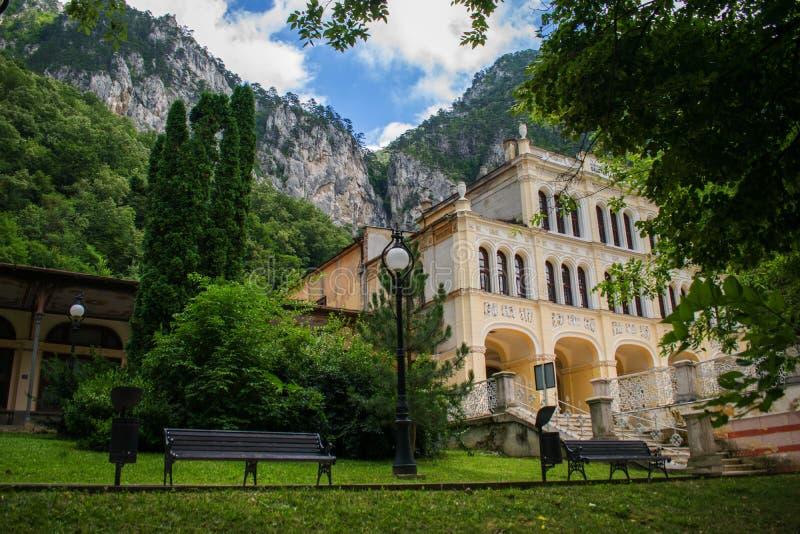 某处一个美丽的公园在山区度假村在罗马尼亚,欧洲 一个美丽的轰烈的大厦、许多绿色树和植物 免版税图库摄影