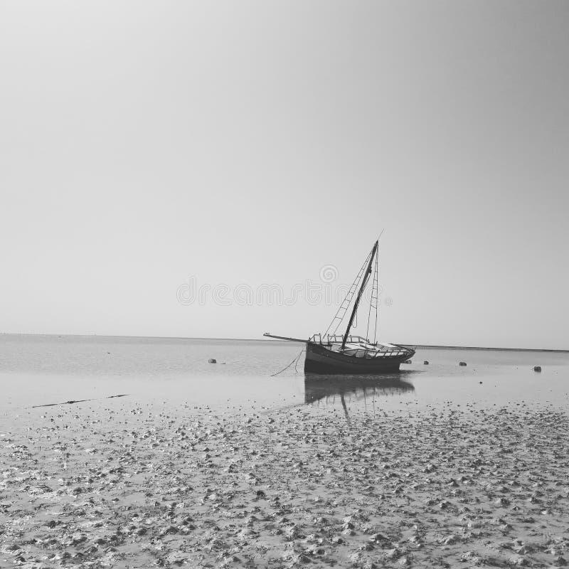 某处在突尼斯在海滩黑白pic的一条小船 免版税库存图片