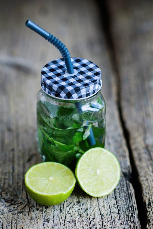 柑桔和草本灌输了戒毒所的sassi水或节食在木板,黑暗的背景的玻璃瓶 免版税库存图片