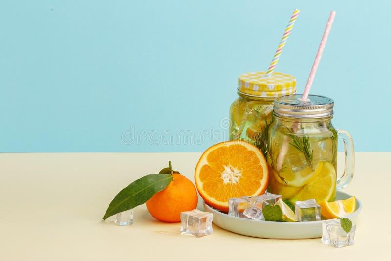 柑橘与柠檬被切的,健康和戒毒所水饮料的柠檬水水在浅兰的背景的夏天 免版税库存照片