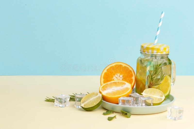 柑橘与柠檬被切的,健康和戒毒所水饮料的柠檬水水在浅兰的背景的夏天 免版税库存图片