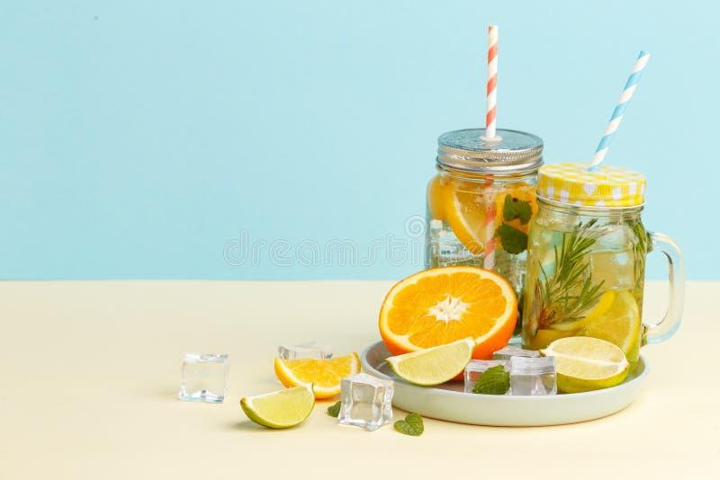 柑橘与柠檬被切的,健康和戒毒所水饮料的柠檬水水在浅兰的背景的夏天 图库摄影