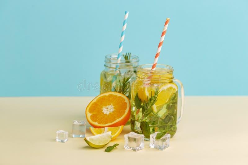 柑橘与柠檬被切的,健康和戒毒所水饮料的柠檬水水在浅兰的背景的夏天 库存图片