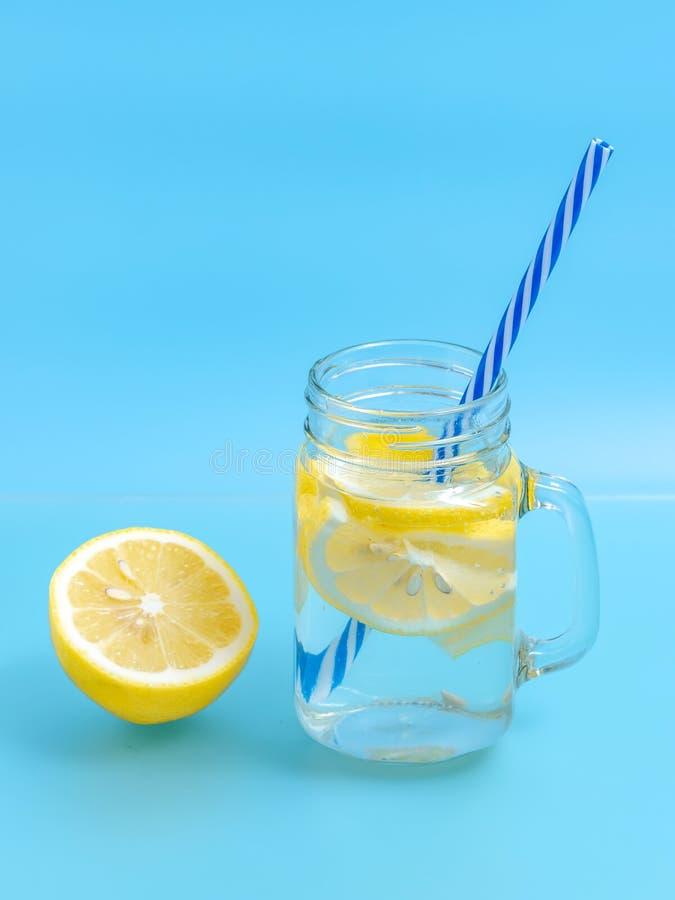 柑橘与柠檬被切的,健康和戒毒所水饮料的柠檬水水在蓝色的夏天照亮背景 库存图片