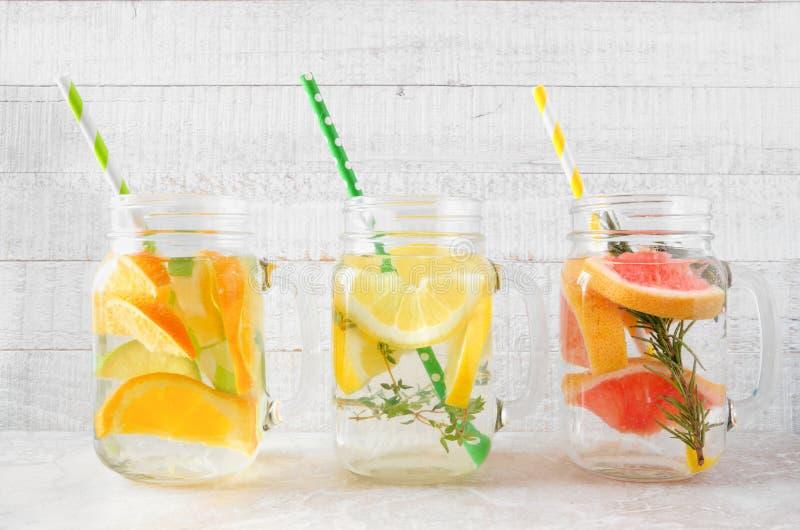 柑橘在金属螺盖玻璃瓶的被灌输的水饮料品种反对白色木头 免版税图库摄影