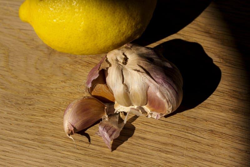 柑橘新鲜的柠檬和的大蒜和放置在木剁委员会的健康食品准备好虚构-食物图象关闭与creat 免版税库存图片