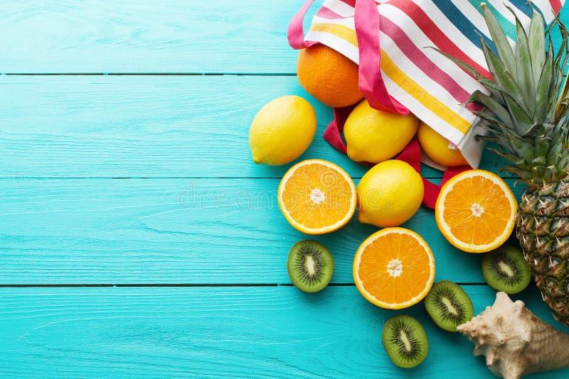 柑橘新鲜食品 您系列节日快乐的夏天 在蓝色木背景的桔子、猕猴桃、菠萝、柠檬和海壳 假期 免版税库存照片