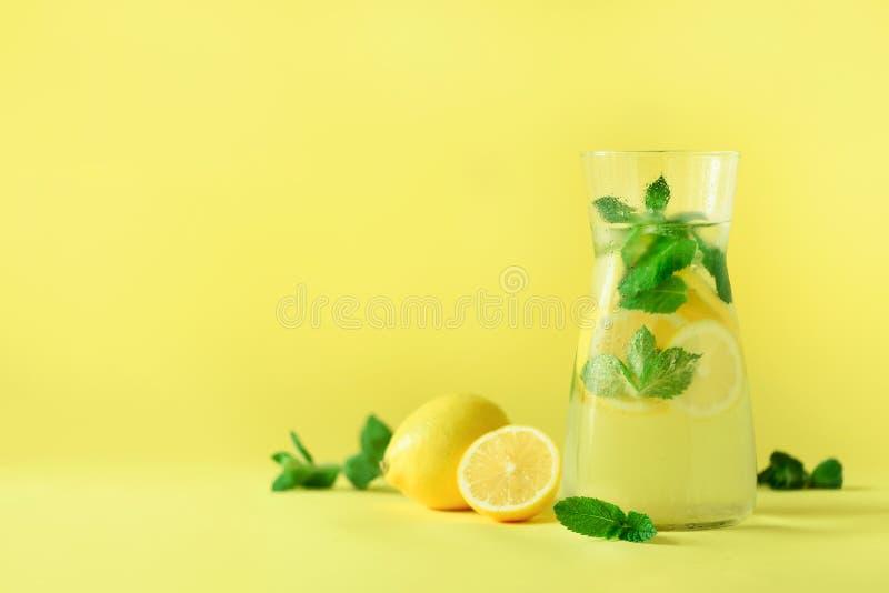 柑橘柠檬水-与冰,薄菏,在黄色背景的柠檬的冷水 戒毒所饮料 夏天果子被灌输的水 复制 免版税库存图片