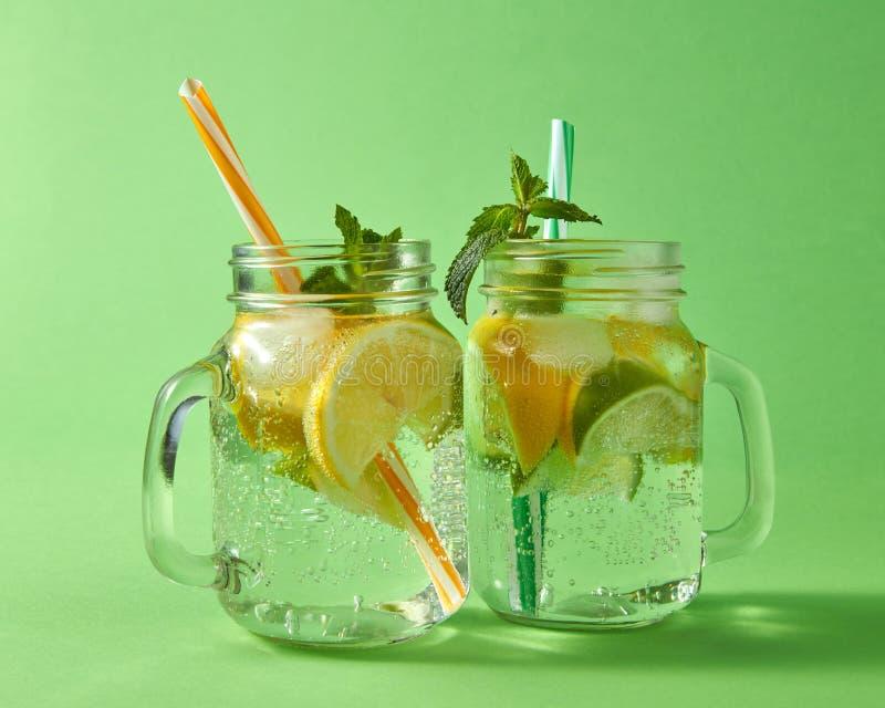 柑橘水果切片在玻璃的柠檬和石灰、冰、水和塑料秸杆在绿色背景 两个金属螺盖玻璃瓶 库存图片