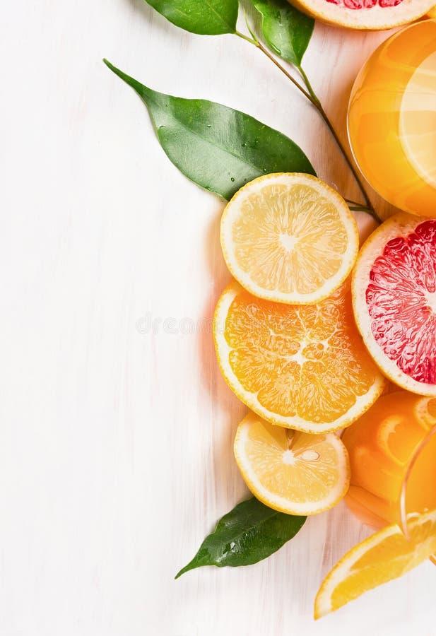 柑橘汁和切的果子:桔子、柠檬和葡萄柚在白色木 免版税图库摄影